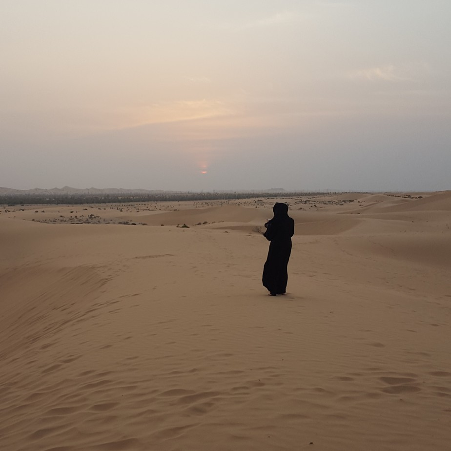 Woman in black abaya in desert